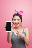 Beautiful young asian woman with pin-up make-up and hairstyle over pink background with mobile phone stock photography