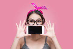 Beautiful young asian woman with pin-up make-up and hairstyle ov. Er pink background with mobile phone Royalty Free Stock Photos