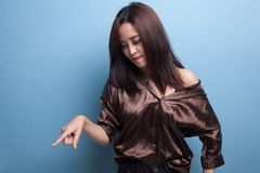 Beautiful young Asian woman point down to blank space. Stock Photos