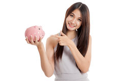Beautiful young Asian woman point to piggy bank Royalty Free Stock Image