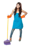Beautiful young asian woman posing hold onto a broom, while smil royalty free stock image