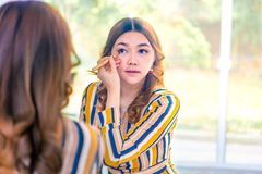 Beautiful young Asian woman putting on her make up in front of her larger bedroom window. With the view of her garden in the background stock photo