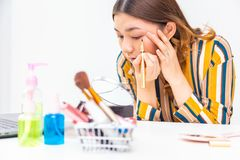 Beautiful young Asian woman putting her make up on stock photography
