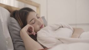 Beautiful young Asian woman reading a book while lying on the bed, Female sleep after relax in bedroom at home. Lifestyle women using relax time at home stock footage