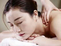 Beautiful young asian woman receiving massage in spa salon royalty free stock photography