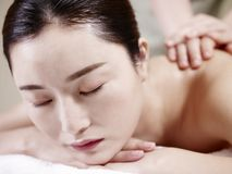 Beautiful young asian woman receiving massage in spa salon royalty free stock images