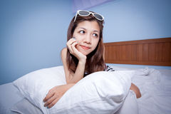 Beautiful young Asian woman relaxing on the bed Stock Image