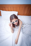 Beautiful young Asian woman relaxing on the bed Stock Photography