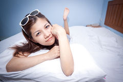 Beautiful young Asian woman relaxing on the bed Stock Photos
