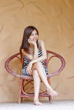 Beautiful young Asian woman relaxing on her chair Royalty Free Stock Image