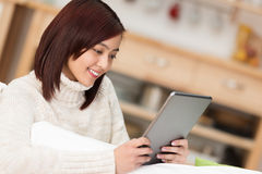Beautiful young Asian woman relaxing with a tablet Royalty Free Stock Photos
