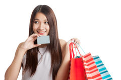 Beautiful young Asian woman with shopping bags and credit card Royalty Free Stock Photo