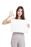 Beautiful young Asian woman show OK with blank sign Stock Photos