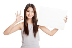 Beautiful young Asian woman show OK with blank sign Stock Image