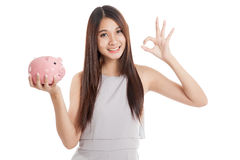 Beautiful young Asian woman show OK with piggy bank Royalty Free Stock Images