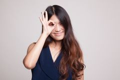 Beautiful young Asian woman show OK sign over her eye. Stock Photos