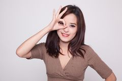 Beautiful young Asian woman show OK sign over her eye. Royalty Free Stock Images