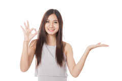Beautiful young Asian woman show palm hand and OK sign Stock Image
