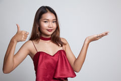 Beautiful young Asian woman show palm hand and thumbs up. Royalty Free Stock Photography