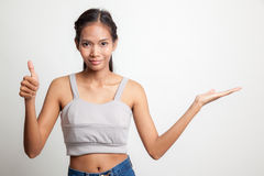 Beautiful young Asian woman show palm hand and thumbs up. Stock Image