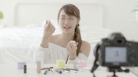 Beautiful young asian woman showing cream or lotion the cosmetic makeup with video and vlog at home