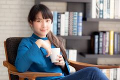 Beautiful young asian woman sitting on chair with comfort and relaxing in living room at home drinking a cup of coffee. Or tea or beverage, lifestyle asia girl stock image