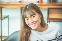 Woman sitting at home and smiling at camera. Beautiful young asian woman sitting at home and smiling at camera royalty free stock photo