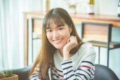 Woman sitting at home and smiling at camera. Beautiful young asian woman sitting at home and smiling at camera stock images