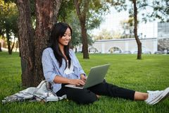 Beautiful young asian woman sitting under a tree and chatting on Stock Image