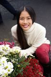 Beautiful young asian woman smiling with flowers at shop Stock Photography