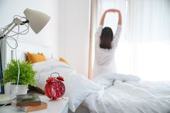 Beautiful young asian woman stretch and relax in bed after wake up morning at bedroom, back view, new day and resting for wellness. Lifestyle concept royalty free stock image
