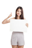 Beautiful young Asian woman thumbs up with blank sign Stock Images