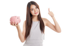 Beautiful young Asian woman thumbs up with piggy bank Royalty Free Stock Images