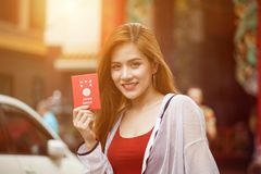 Beautiful Young Asian women tourist traveler with backpack smiling and show passport of Japan in China town market culture. Beautiful Young Asian woman tourist royalty free stock photography