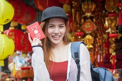 Beautiful Young Asian women tourist traveler with backpack smiling and show passport of Japan in China town market culture. Beautiful Young Asian woman tourist royalty free stock images