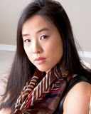 Portrait of lovely Asian woman with scarf. Beautiful young Asian woman turns her head to the camera in this gentle image royalty free stock photos