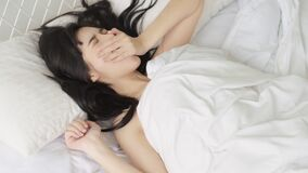 Beautiful young asian woman waking up in the morning with happy and yawn on bed in the bedroom