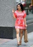 Beautiful young Asian woman waving at someone Stock Photos