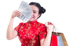 Beautiful Young asian woman wear chinese dress traditional cheongsam or qipao with Carrying a shopping bag and dollar banknote. And smile. Chinese New Year Stock Image