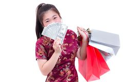 Beautiful Young asian woman wear chinese dress traditional cheongsam or qipao with Carrying a shopping bag and dollar banknote. Chinese New Year Festivities Royalty Free Stock Photography