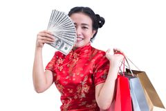 Beautiful Young asian woman wear chinese dress traditional cheongsam or qipao with Carrying a shopping bag and dollar banknotes. And smile. Chinese New Year Royalty Free Stock Photography