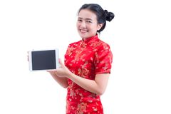 Beautiful Young asian woman wear chinese dress traditional cheongsam or qipao. Hand holding blank screen digital tablet. Isolated on white background, Concept Royalty Free Stock Image