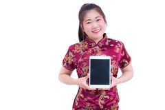 Beautiful Young asian woman wear chinese dress traditional cheongsam or qipao. Hand holding blank screen digital tablet. Isolated on white background, Concept Stock Photography