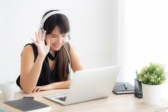 Beautiful young asian woman wear headphone smiling say hello using chat video call on laptop computer royalty free stock photo