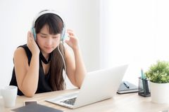 Beautiful young asian woman wear headphone smiling say hello using chat video call on laptop computer. Girl relax enjoy listening music online, education royalty free stock images