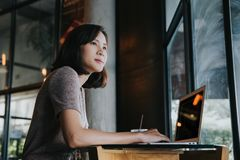 Beautiful young Asian woman working at a coffee shop with a laptop stock photography