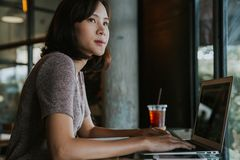 Beautiful young Asian woman working at a coffee shop with a laptop royalty free stock images