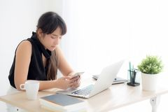 Beautiful young asian woman working laptop computer online to internet and texting message on smart mobile phone. Freelance using notebook, business and royalty free stock photos