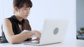 Beautiful young asian woman working and typing with laptop at office stock video footage