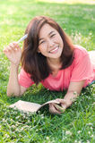 Beautiful young asian woman writing in her notebook on the meadow Royalty Free Stock Photo
